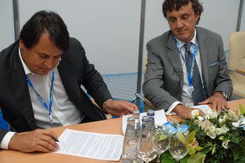 Рустам Тарико (слева) и Эдуард Таран подписывают меморандум, который расширит взаимодействие бизнес-структур, находящихся под их контролем.