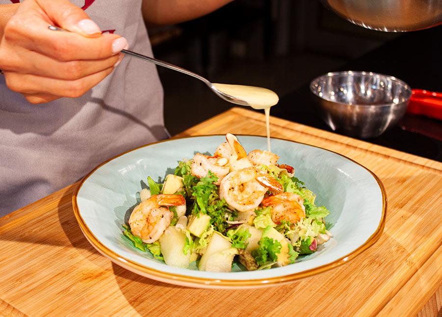 Поливаем салат заправкой и приправляем свежемолотым черным перцем