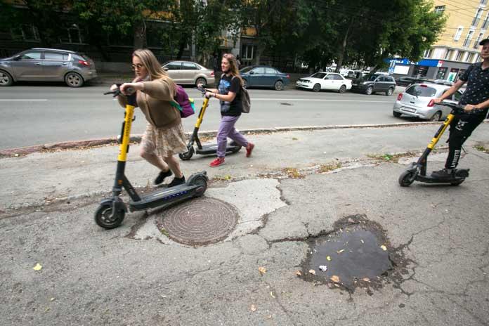 Электросамокаты едут по разбитому тротуару